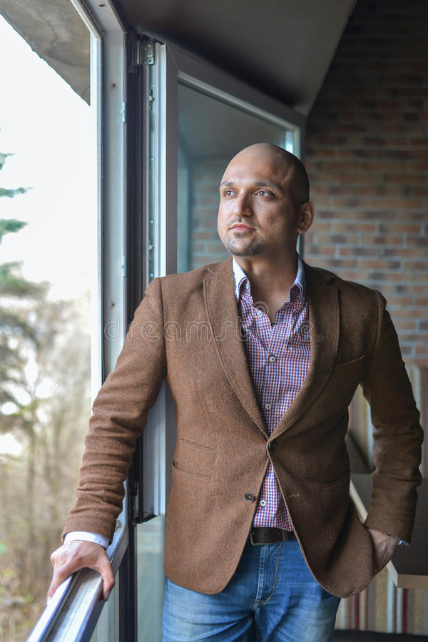 Handsome indian businessman, standing near panoramic window, thinking, stock images
