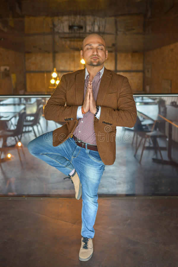 Handsome indian businessman weared in suit performing yoga or asana to relax, eyes closed stock images