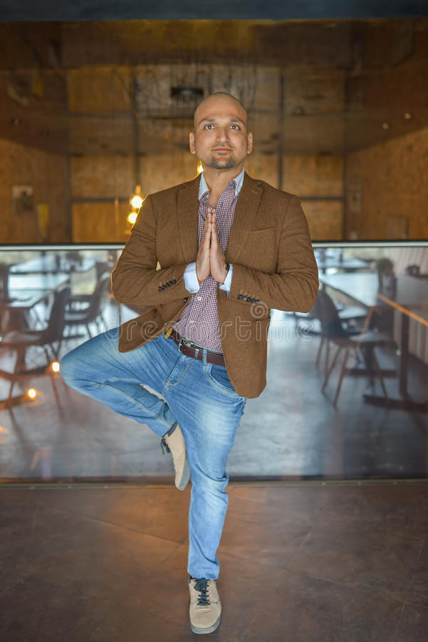 Handsome indian businessman weared in suit performing yoga or asana to relax, smiling lloking at camera royalty free stock photo