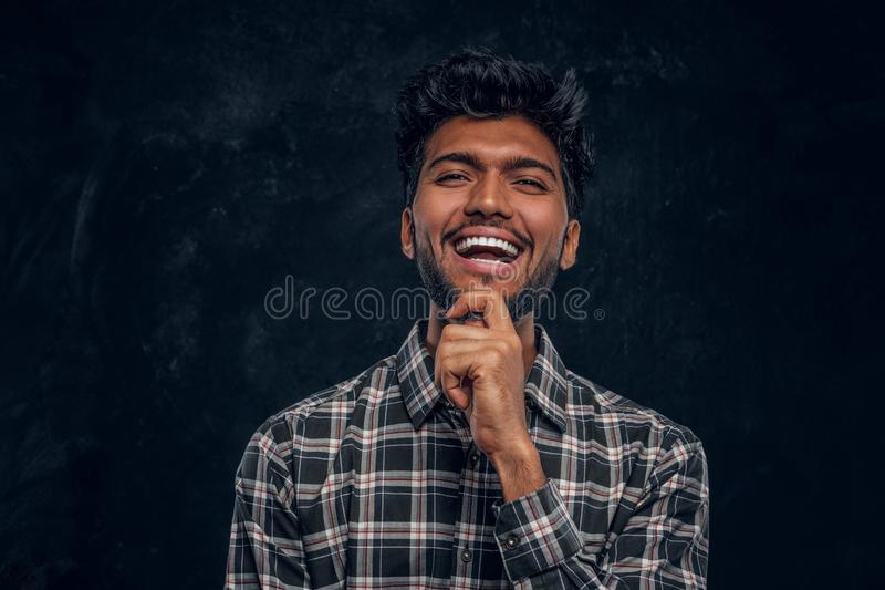 Handsome Indian guy in plaid shirt smiling and holds his hand on chin. Studio photo against a dark textured wall royalty free stock image