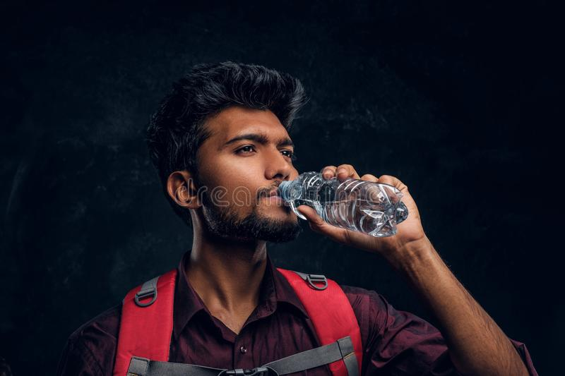 Indian hiker with backpack exhausted with thirst drinking water. Studio photo against a dark textured wall. Handsome Indian hiker with backpack exhausted with stock photos