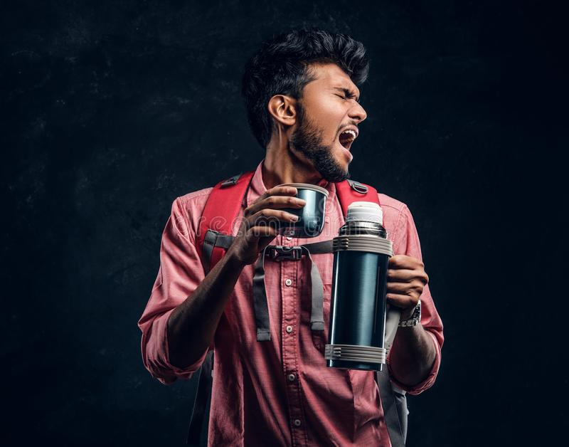 Handsome Indian hiker with backpack got a stirring sensation drinking a tea from a thermos. Studio photo against a dark textured wall stock photo