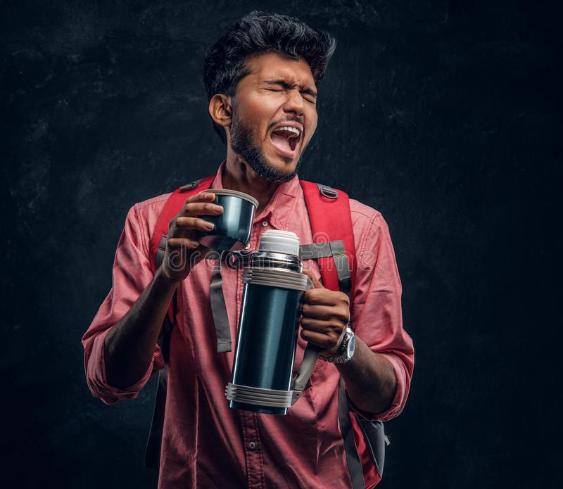 Handsome Indian hiker with backpack got a stirring sensation drinking a tea from a thermos. Studio photo against a dark textured wall stock photography