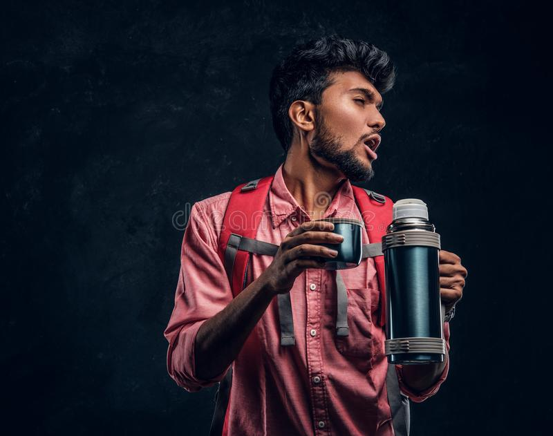 Handsome Indian hiker with backpack got a stirring sensation drinking a tea from a thermos. Studio photo against a dark textured wall royalty free stock photo
