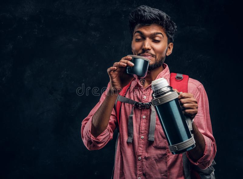 Handsome Indian hiker with backpack got a stirring sensation drinking a tea from a thermos. Studio photo against a dark textured wall stock images