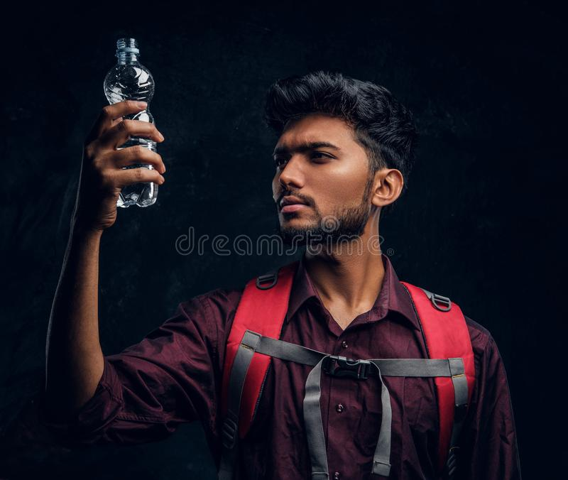 Indian hiker with backpack holding a bottle of water looking at her. Studio photo against a dark textured wall. Handsome Indian hiker with backpack holding a royalty free stock photography