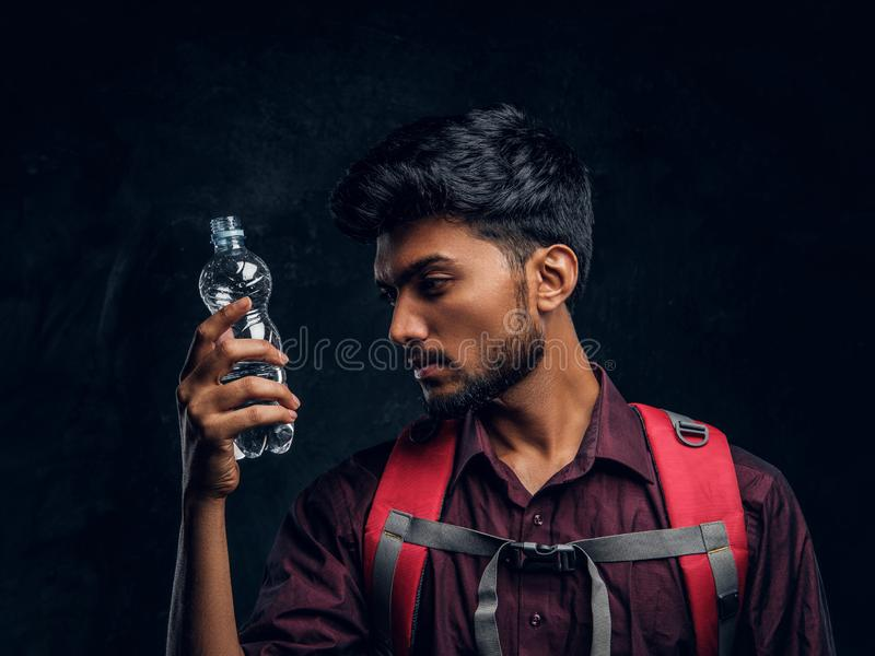Indian hiker with backpack holding a bottle of water looking at her. Studio photo against a dark textured wall. Handsome Indian hiker with backpack holding a stock photography