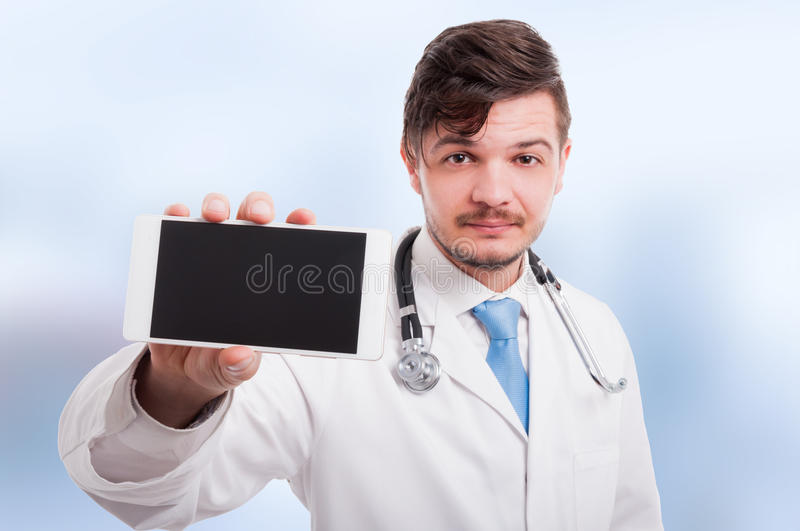 Handsome intern shows the phone with blank screen royalty free stock photo