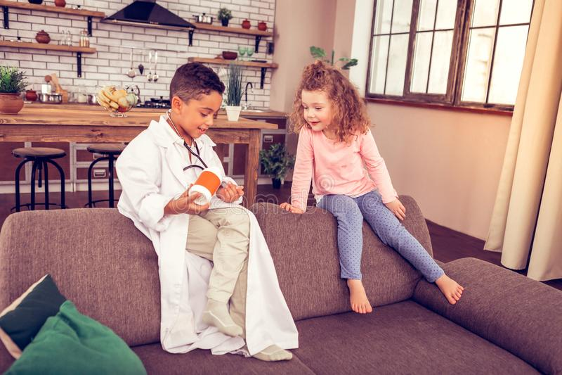 Handsome international kid looking at bottle with pills. Medical care. Pleased curly-haired child expressing positivity while sitting near her doctor stock photography