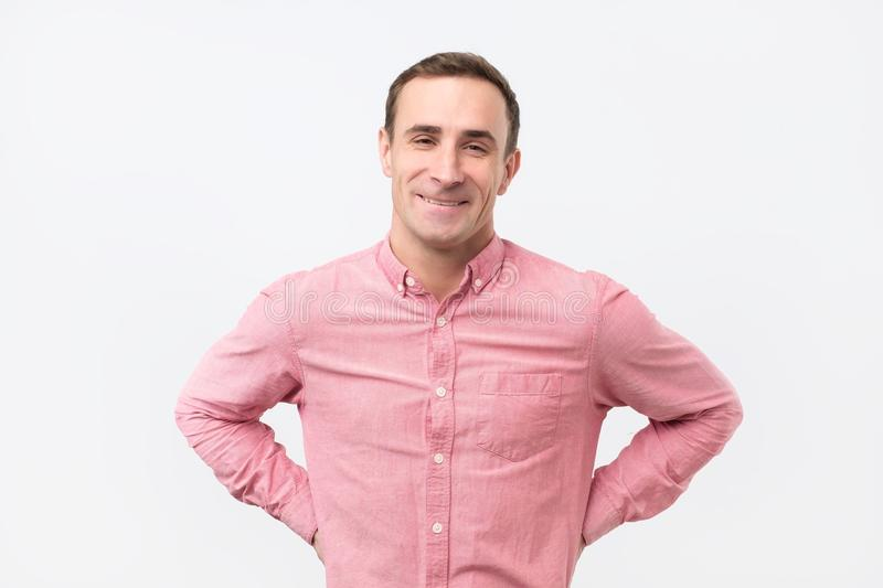 Handsome italian man wearing pink shirt with slight smile posing against white background stock photos