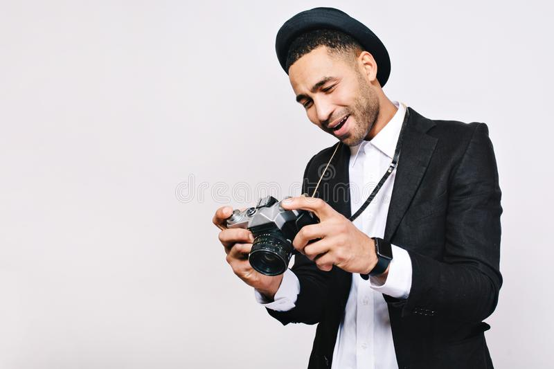 Handsome joyful guy in suit, hat looking at camera in hands on white background. Travelling, tourist, having fun, retro royalty free stock image