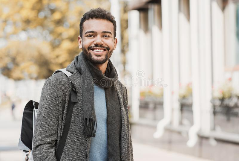 Handsome joyful man autumn portrait. Smiling men student wearing warm clothes in a city in winter royalty free stock photo