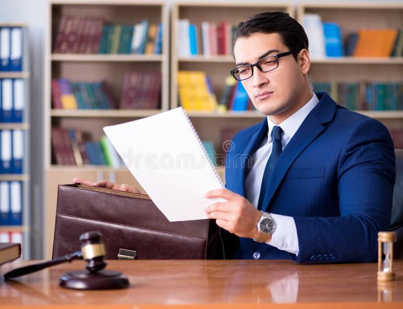 Handsome judge with gavel sitting in courtroom royalty free stock photo