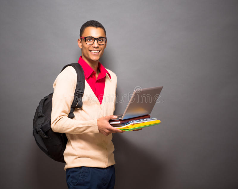 Handsome latin student with laptop computer in studio royalty free stock photography