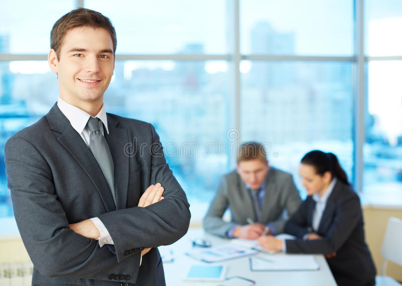 Handsome leader. Image of cross-armed leader looking at camera in working environment royalty free stock photos