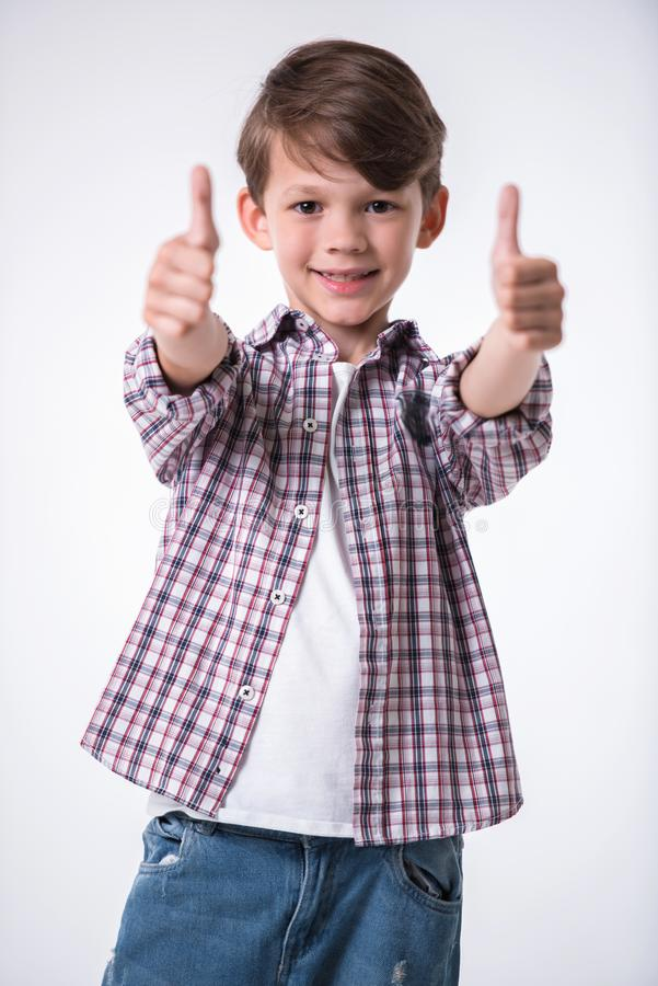 Handsome little boy. Is showing thumbs, looking at camera and smiling, on light background royalty free stock photos