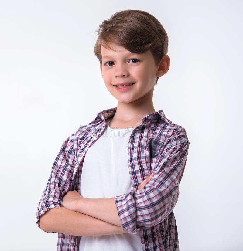 Handsome little boy. Is looking at camera and smiling while standing with crossed arms on light background stock images