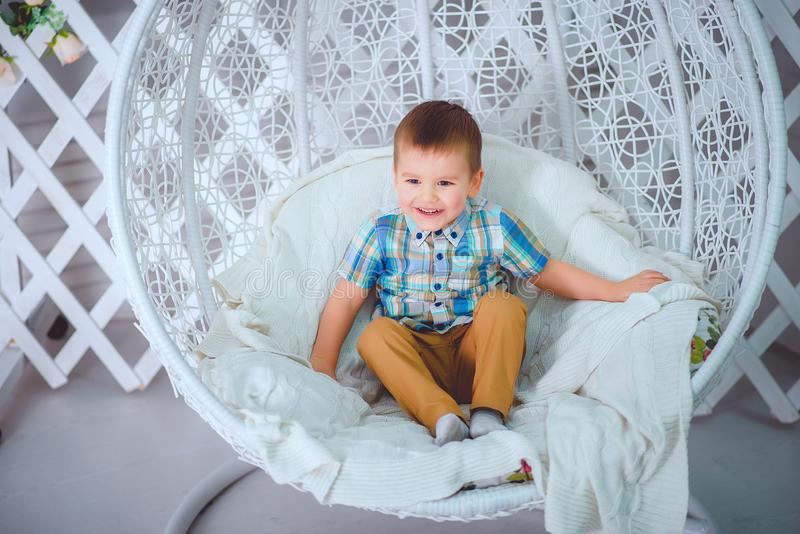 Handsome little boy sitting on a swing smiling posing in the Studio royalty free stock photos