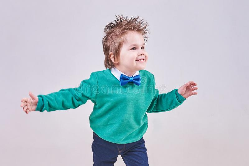 A handsome little boy, wearing a blue bow tie and a green sweater, dances and smiles royalty free stock photo