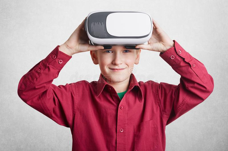 Handsome little male child wears VR glasses, has fun and entertains himself, plays video games, isolated over white background. Sm stock photography