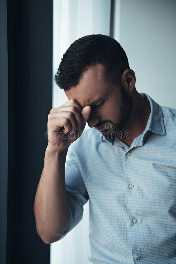 handsome lonely man in bad mood standing near window stock photo