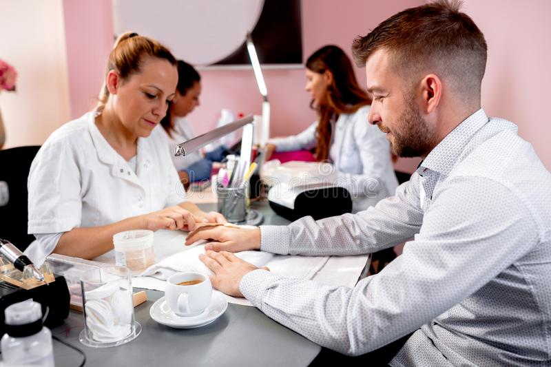 Handsome looking guy having a manicure treatment royalty free stock photography