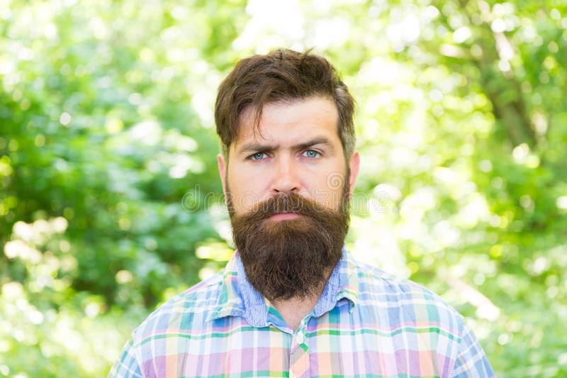 Handsome lumberjack. Man beard and mustache in summer forest. Hike and travel. Summer vacation concept. Man bearded. Hipster green trees background. Guy relax stock photography