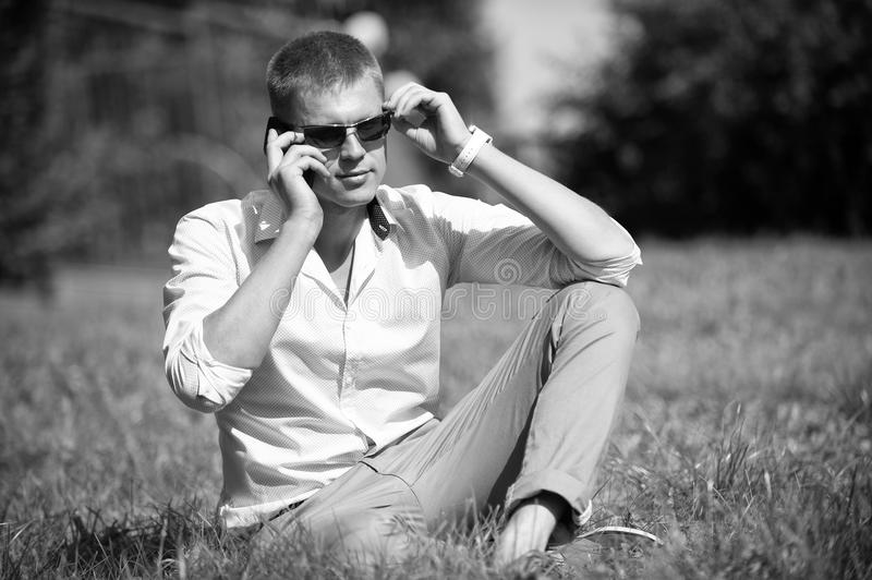 Handsome macho enjoy summer day. Businessman in sunglasses on sunny outdoor. Man relax on green grass. Fashion style and royalty free stock image
