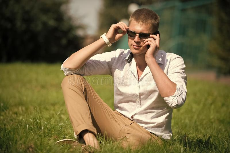 Handsome macho enjoy summer day. Businessman in sunglasses on sunny outdoor. Man relax on green grass. Fashion style and stock photos