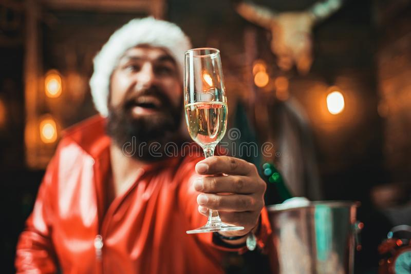 Handsome macho man wearing Santa clothes. Man with beard holds glass of champagne. Holidays. Handsome macho man wearing Santa clothes. Man with beard holds royalty free stock images