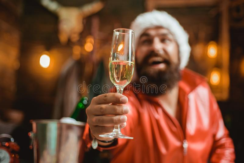Handsome macho man wearing Santa clothes. Man with beard holds glass of champagne. Holidays. Handsome macho man wearing Santa clothes. Man with beard holds stock photo