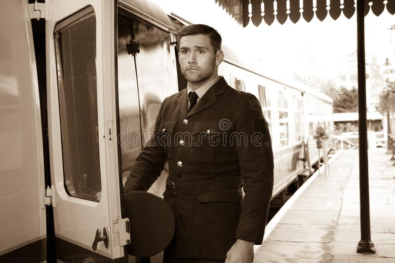 Handsome male British officer in vintage uniform at train station next to train stock photography
