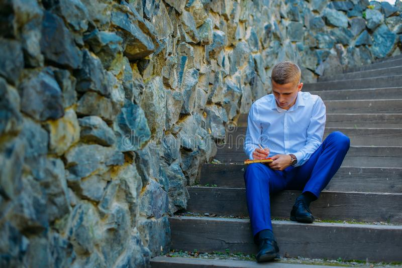 Handsome male business executive sitting on stairs outside making his plans stock photo