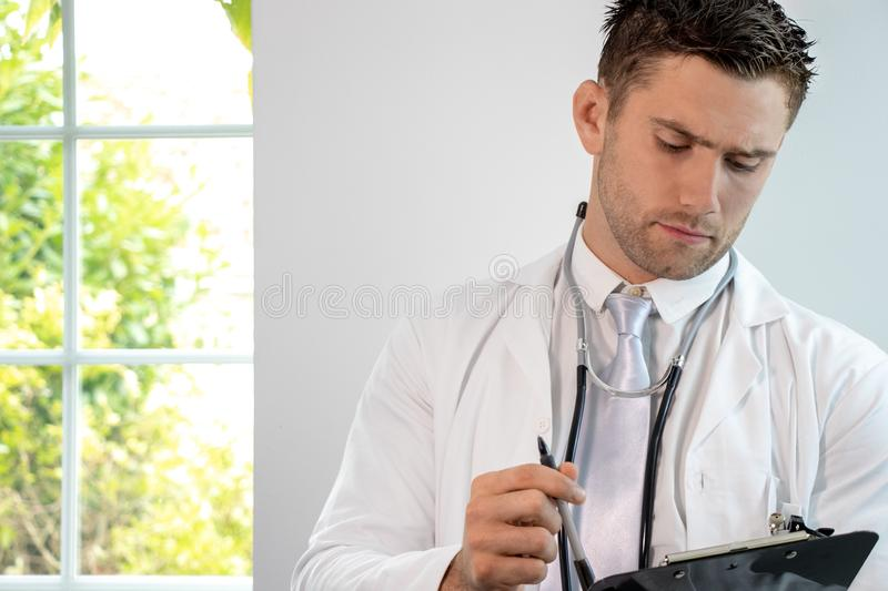 Good looking male doctor, gp, with stethoscope and clipboard royalty free stock images