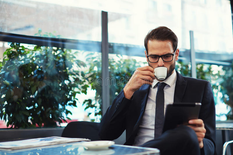 Handsome male drinking tea and reading news about business and finance. Attractive and smart business man using his tablet while having breakfast at coffee shop royalty free stock photo