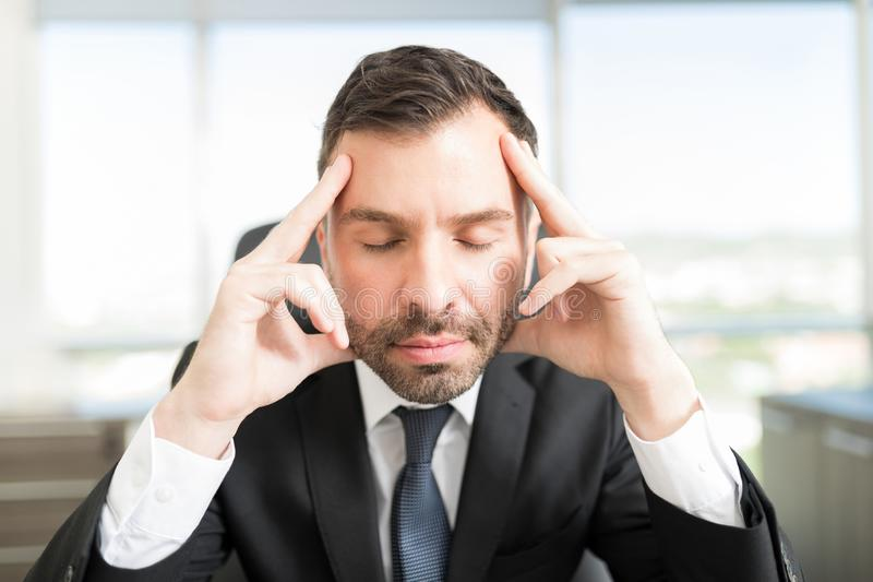 Handsome Male Executive Meditating At Workplace royalty free stock image