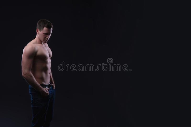 Handsome male fitness model showing naked torso, muscular body. Strong hands, chest and shoulder muscles and biceps. Studio shot o. N black background, copy stock images
