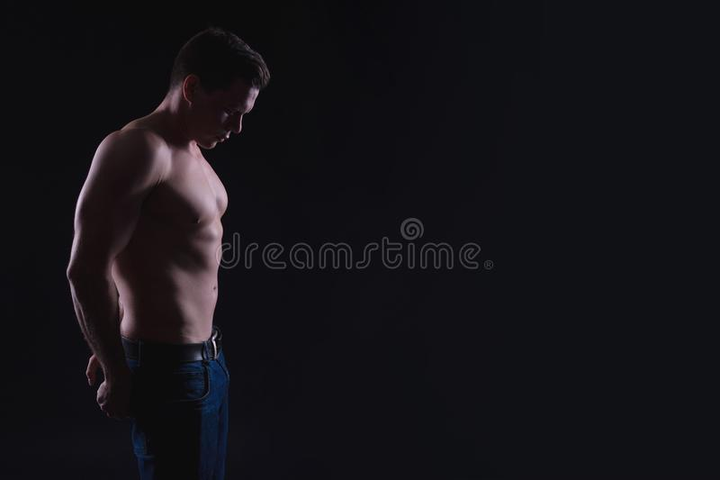 Handsome male fitness model showing naked torso, muscular body. Strong hands, chest and shoulder muscles and biceps. Studio shot o. N black background, copy royalty free stock image