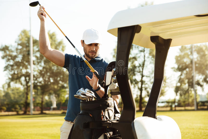 Handsome male golfer taking clubs from a bag in a golf cart. At the green course royalty free stock image