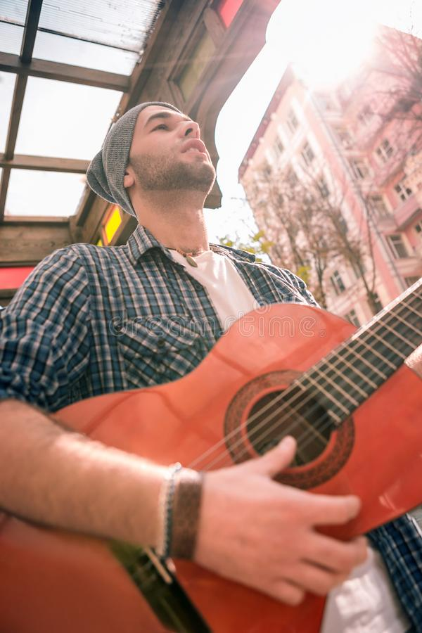 Handsome male guitarist developing skills on street stock photos