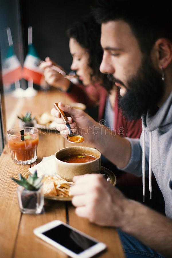 A handsome male hipster with a beard eating a hot soup at a cafe, lunch break stock photos