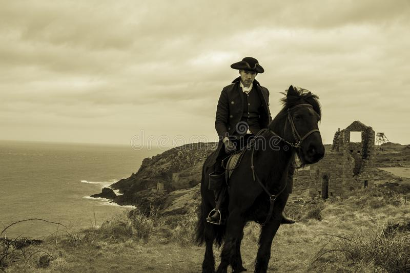 Handsome Male Horse Rider Regency 18th Century Poldark Costume with tin mine ruins and Atlantic ocean in background royalty free stock photo