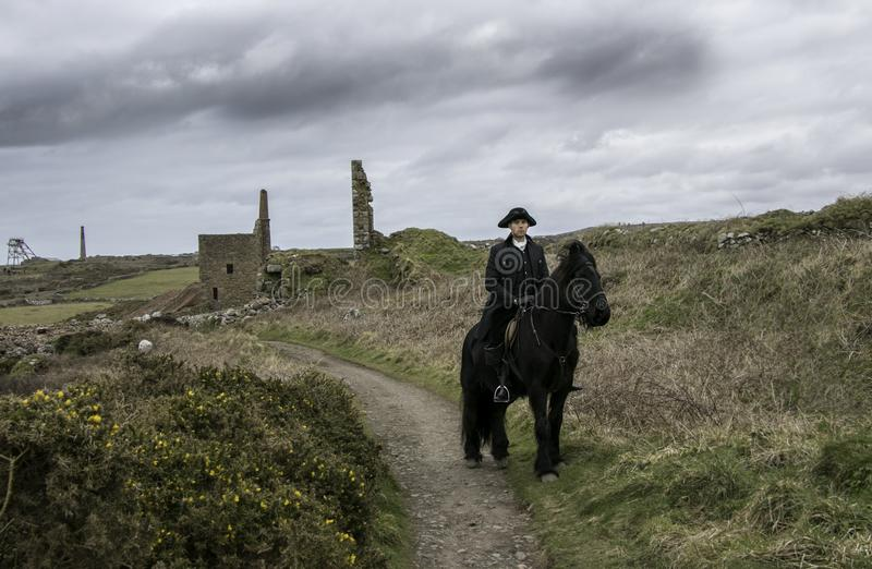 Handsome Male Horse Rider Regency 18th Century Poldark Costume with tin mine ruins and countryside in background stock image