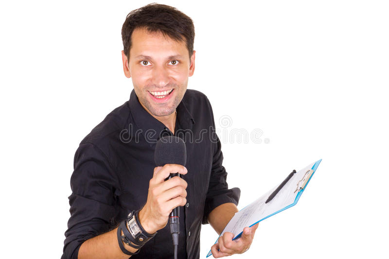 Handsome male journalist reporting news on microphone with notes royalty free stock photography