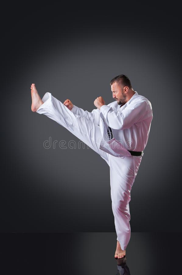 Handsome male karate player doing kick on the gray background royalty free stock photo