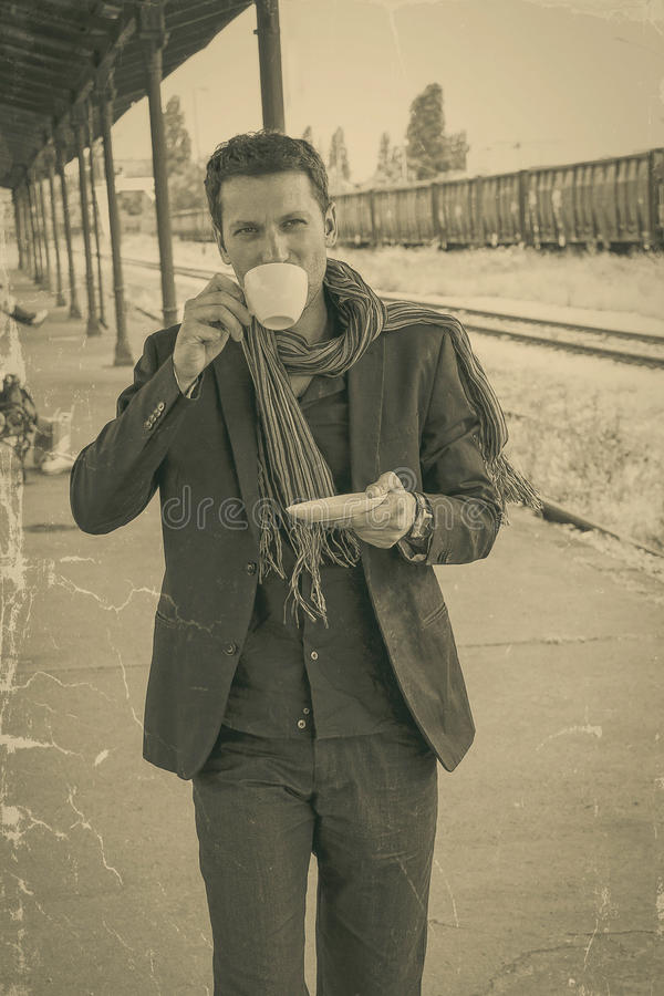 Handsome male model drinking coffee at train station stock photos