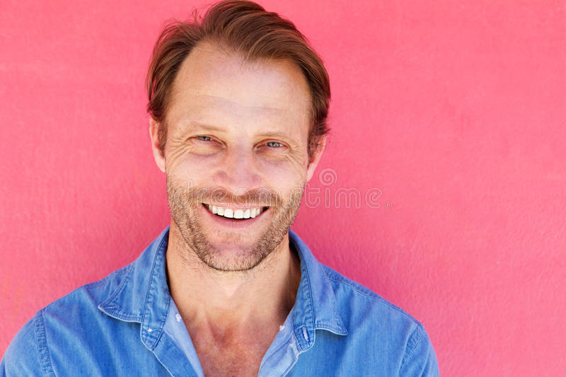 Handsome male model smiling against pink background royalty free stock image