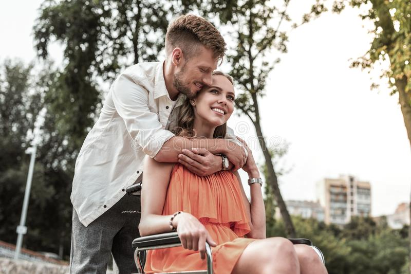 Handsome male person expressing love to his girl. Warm hugs. Amazing female expressing positivity while looking upwards, sitting on wheelchair royalty free stock images