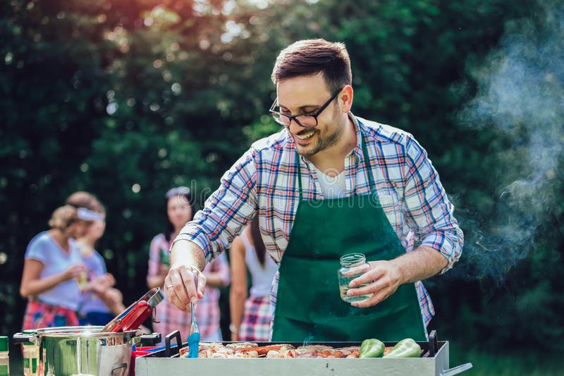 Man preparing barbecue outdoors for friends royalty free stock image