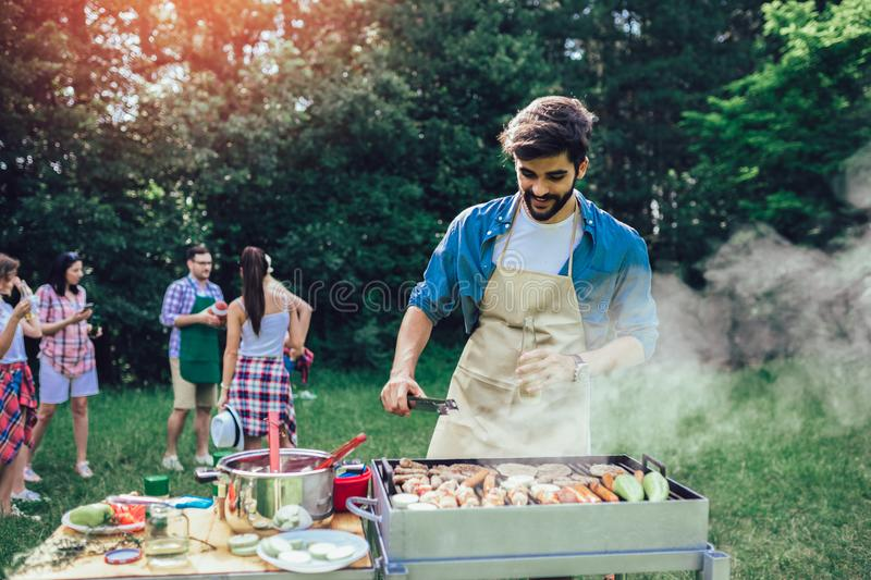 Man preparing barbecue outdoors for friends stock photos